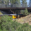 Durango & Silverton NG Railroad train passing under bridge on US 550 in Colorado.