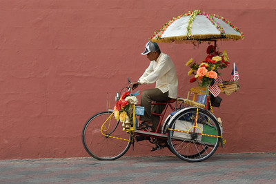 Colourful tricycles in Melaka, Malaysia are used to carry tourists around the city. The interesting decoration draws attention.