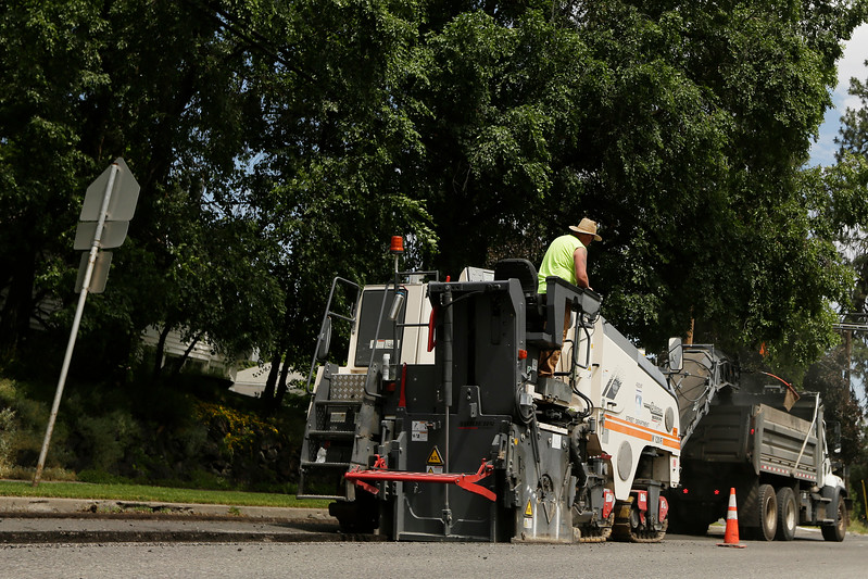 A City of Spokane street crew grinds the top layer of E. 17th Ave., near S. Regal St. in preparation for new asphalt in Spokane, Wash., Monday, June 26, 2017. (Young Kwak)