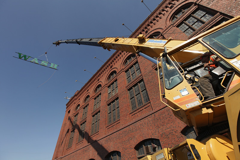 Rhodes Crane & Rigging, Inc.'s Roger Baker uses a Grove Worldwide RT64C to remove a sign from the Washington Water Power building, in Spokane, Wash., on Wednesday, August 28, 2013. (Young Kwak/The Pacific Northwest Inlander)