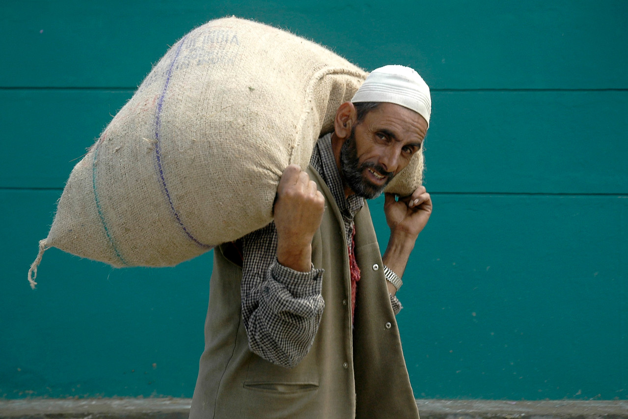 Man carrying a sack of grains on his back in Pahalgao, Kashmir, J&K