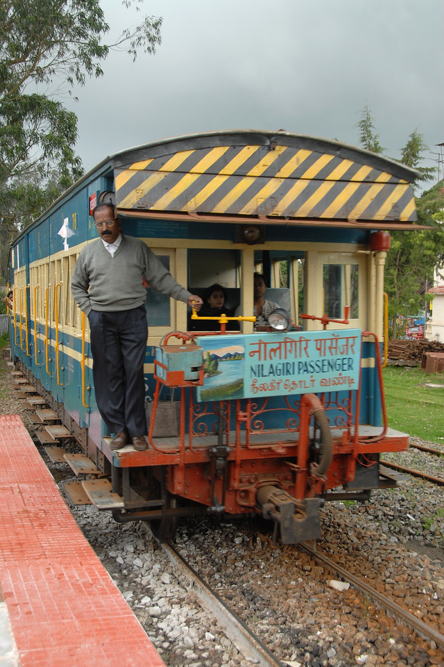 The small train which is part of the NMR (Nilgiri Mountain Railways) arrives into Ooty railway station. For the Niligiri Passenger Train (NMR) this station is the starting point for the train to go to Mettupalayam (near Coimbatore). It was sheer joy to travel on the meter gauge steam locomotives which is one of the oldest mountain railways in India (since 1899). In July 2005, UNESCO added the NMR as an extension to the World Heritage Site of Darjeeling Himalayan Railway.<br /> Ooty, Tamil Nadu, India. July 2007