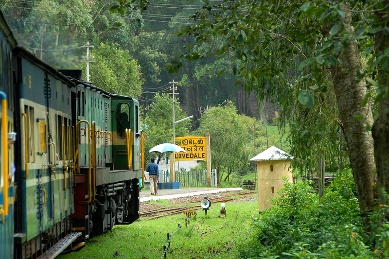 Lovedale Station on the Niligiri Passenger Train from Udagamandalam to Mettupalayam. As the Niligiri Mountain Railways (NMR) as it makes its way through the hills & mountains it passes a number of tunnels while taking about about 3.5 hrs to go to Mettupalayam (near Coimbatore) from Ooty. Its a joy to travel on the meter gauge steam locomotives which is one of the oldest mountain railways in India (since 1899). In July 2005, UNESCO added the NMR as an extension to the World Heritage Site of Darjeeling Himalayan Railway.<br /> Ooty, Tamil Nadu, India. July 2007