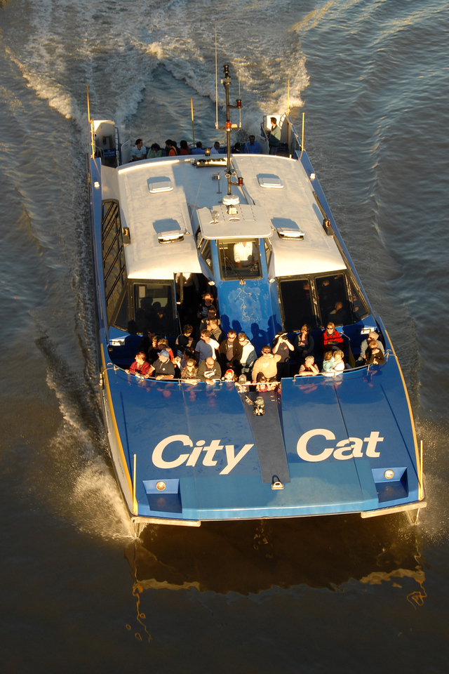 As the Sun sets, the City Cat - water taxi service in Brisbane, Australia continue to ferry passengers.