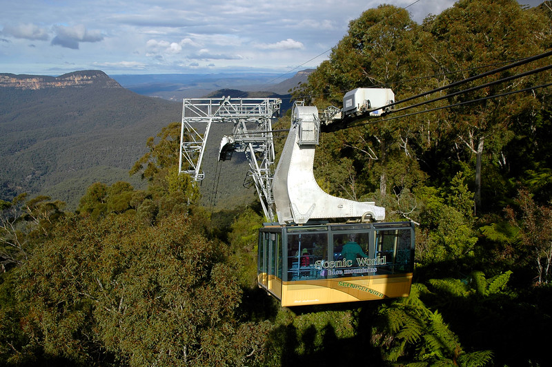 The Scenic World Skyway: a glass-bottom aerial cable car that traverses an arm of the Jamison Valley at Katoomba near the Three Sisters. This is a famous rock formation in the Blue Mountains of New South Wales, Australia. They are close to the town of Katoomba and are one of the Blue Mountains' most famous sights, towering above the Jamison Valley. Their names are Meehni (922 m), Wimlah (918 m), and Gunnedoo (906 m).<br /> <br /> The Sisters were formed by erosion. The soft sandstone of the Blue Mountains is easily eroded over time by wind, rain and rivers, and the cliffs surrounding the Jamison Valley are being slowly broken up. Formations like the Three Sisters are created when water seeps into small cracks in the rock, gradually enlarging them over time to form large indentations. Eventually, the Sisters will be eroded away completely.