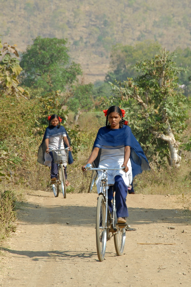 Girls cycle to their school wearing school uniform in a village near Nagpur, Maharashtra, MH, India.