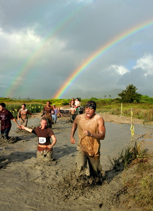 "A bright hawaii rainbow shines above the muddy competitors in Hawaii's  10th Annual, Combat Service Support Group 3, Swamp Romp  June 19, 2004 at Marine Corps Base Hawaii in Kaneohe, Hawaii. Both military and civilian teams compete in a race that is designed to simulate the ""Marine Experience"". The 5-mile course takes competitors through mud, dirt, sand  and water, and over obstacles including climbing walls, low crawls, simulated machine gun rounds and a rope swing.  Well over 5, 000 Hawaii US military are presently deployed in support of Operation Iraqi Freedom- the largest deployment for the state since Vietnam. REUTERS/Lucy Pemoni"