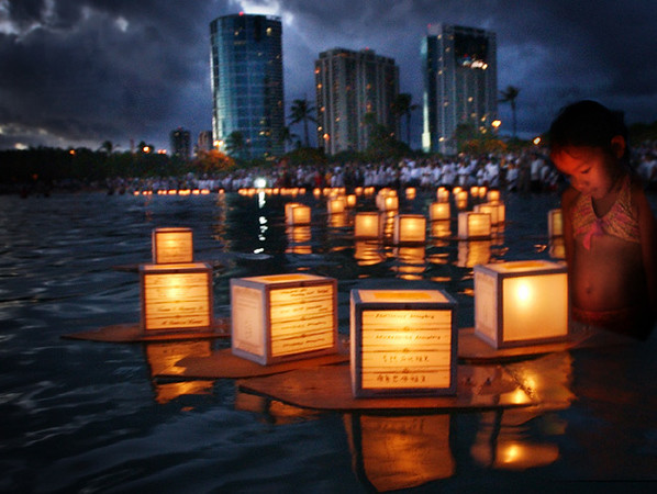 """Hundreds of lanterns float in the waters off of Magic Island in Ala Moana Park in Honolulu, Hawaii, May 31, 2004 during the annual Toro-Nagashi (Lantern Floating) Ceremony. The lanterns with names of family and friends who have gone from this world are set afloat in the shores of the Pacific Ocean to serve as beacons to their dead souls so they can find their way back to the spirtual world. The Lantern Floating Ceremony, organized by the Shinnyo-en temple of Hawai'i, precedes the Obon Festival or """"Feast of the Dead"""". The ceremony is also held on Memorial Day weekend to pray for the souls of the war dead and highlight the need for world peace. REUTERS/Lucy Pemoni"""