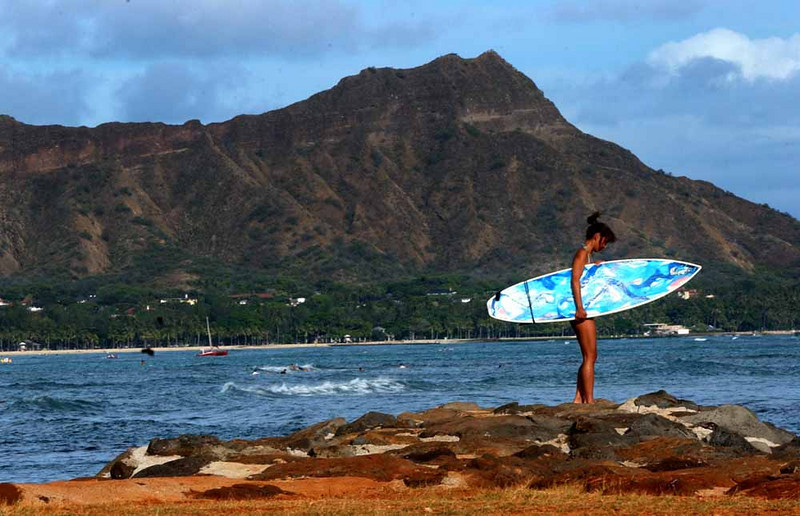 Satsuki Okubo, 33,  of Kanagawa, Japan inspects the waters from a rocky ledge with her brightly painted blue surfboard on Magic Island near Waikiki Beach in Honolulu, Hawaii, June 23, 2004. The famous landmark, Diamond Head Mountain, a dorment volcano frames Okubo in the background. Hawaii is the birthplace of surfing which is still popular with local residents and tourists worldwide. Only recently (MAY 28?) however did surfing become santioned as official high school sport by the Hawaii Board of Education. The decision whether to have a surfing team will be up to each  individual Hawaii high school. Hawaii never recognized interscholastic high school surfing teams in the past because of concerns over liability and safety. (Reuters/Lucy Pemoni