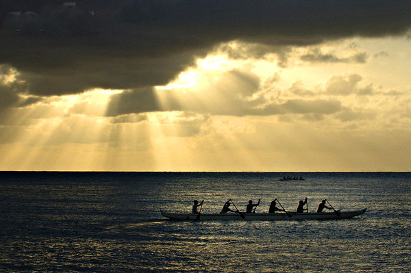16 Jun 2006, Haleiwa, Oahu, Hawaii, USA --- Sun shines over outrigger paddlers practicing on the North Shore of the island of Oahu, in Haleiwa, Hawaii, June 15, 2006. During the winter the North Shore is known for it's massive and dangerous wave breaks, but in the summer, canoes and swimmers enjoy the seas.  REUTERS/Lucy Pemoni (HAWAII) --- Image by © LUCY PEMONI/X01574/Reuters/Corbis