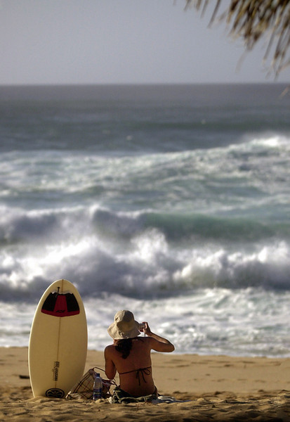 A young women takes a picture of the 5 to 15 foot waves that hit the north and western shores of Oahu, Feb. 19, 2004 at Sunset Beach, Hawaii. A high surf advisory is in effect and is expected to continue tomorrow. REUTERS/Lucy Pemoni