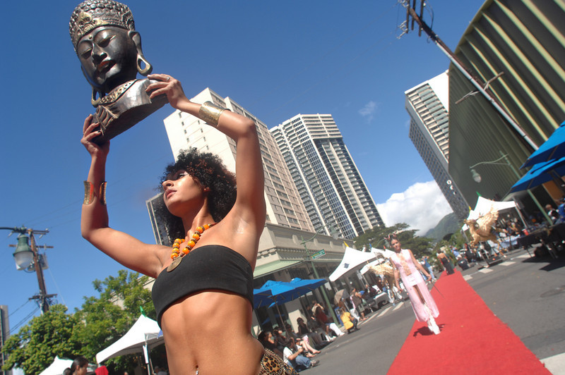 Tiana De Bell carries a Buddha's head  while walking the red carpet for fashion designers 'Bad Sushi' on the streets of Chinatown in Honolulu, Hawaii, Oct 13, 2007. De Bell was one of dozens of models participating the frist annual Honolulu Fashion Week  with in an outdoor show of Hawaii's leading and upcoming fashion designers work in the historic downtown district. REUTERS/Lucy Pemoni