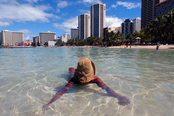 ** ADVANCE FOR SUNDAY RELEASE AUG. 14 **Paradise Ellis of Honolulu finds a spot in the early morning water away from the growing crowds, Thursday, Aug. 11, 2005 on Waikiki Beach in Honolulu. Tourists are flocking to Hawaii in record numbers. Part of the reason for the tourism boom in the islands is because of the global unrest and terror attacks, which have persuaded many Americans who ordinarily would go abroad to instead seek an exotic destination<br /> within U.S. borders. (AP Photo/Lucy Pemoni)