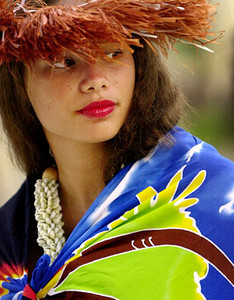 Maraeura Peyroux, 15 of the Cook Island peers out from under her Kiriau hat while waiting to preform tradtional Rarotongan hula on Waikiki Beach in Honolulu, Hawaii, May 17, 2004.  Peyroux was waiting for her Rarotongan Dance troup,Tamariki Manuia, to start their sunset torchlighing performance. The 27- member group with five musicians and 12 dancers performs traditional drums, music dances and songs. The group was on Oahu to perform in the Polynesian cultural Center's annual Fireknife Competition.  REUTERS/ Lucy Pemoni
