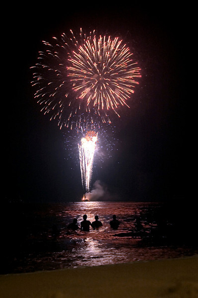Spectators in the waters off of Waikiki Beach watch New Years Eve fireworks shot off a barge in Honolulu, Hawaii, Jan.1, 2007.  REUTERS/Lucy Pemoni