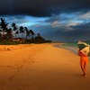 A women walking with an umbrella along the shoreline of Lanikai Beach during a brief sunrise sunshower in Kailua, Hawaii, Friday, May 28, 2004.  REUTERS/Lucy Pemoni