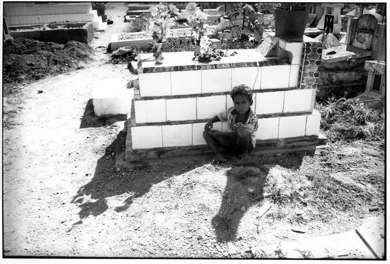 Boy waiting beside beside a grave in Santa Cruz cemetery, site of the massacre in 1991