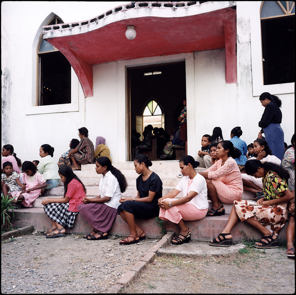 Praying outside a packed Balide church.