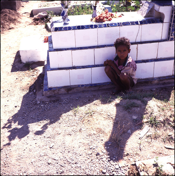 Boy waiting by a grave in Santa Cruz cemetery, site of the 1991 massacre.