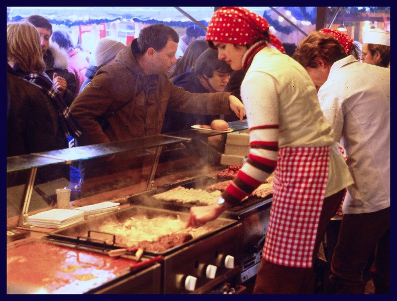Women frying food during Weihnachtsmarkt (a street market associated with the celebration of Christmas during the four weeks of Advent).