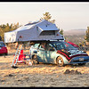 A small car with a big rooftop tent