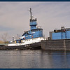 Great Lakes Ore/Gravel ship entering Muskegon Lake pushed by the tugboat Rebecca Lynn.