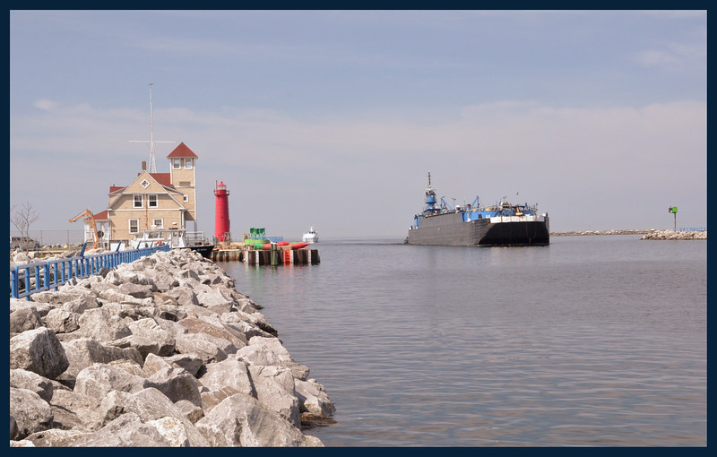 The Muskegon South Pierhead Lighthouse and a Great Lakes Ore/Gravel ship entering Muskegon Lake pushed by the tugboat Rebecca Lynn.