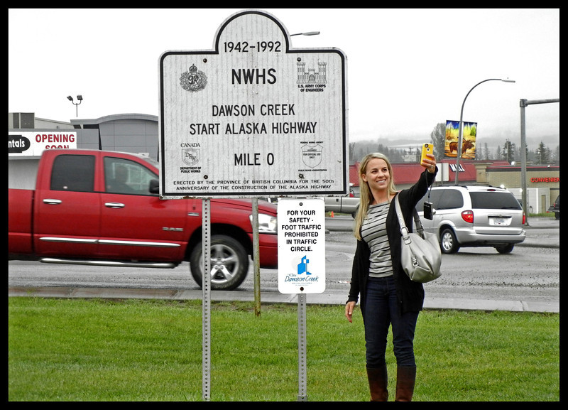 "Young woman standing in front of the ""Start of the Alaska Highway"".  She is good at ""selfies"", but not so good at reading signs."