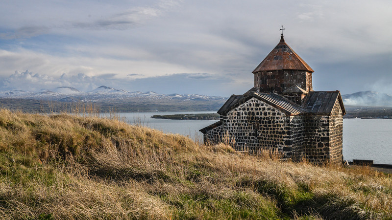 The ancient monastery at Sevanavank overlooks lake Sevan and distant snowy hills.