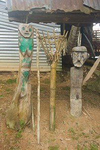 Iban Village near Batang Ai, Malaysia - The center post is used for offerings to keep evil spirits away. Just in case, it is 'protected' by two carved posts to keep any demons from harming the village.