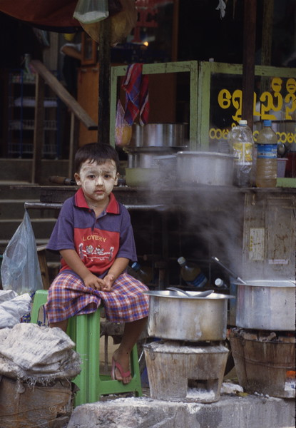 A boy posed in a local cooking stall, while his mother prepared foods for sale to the general public.
