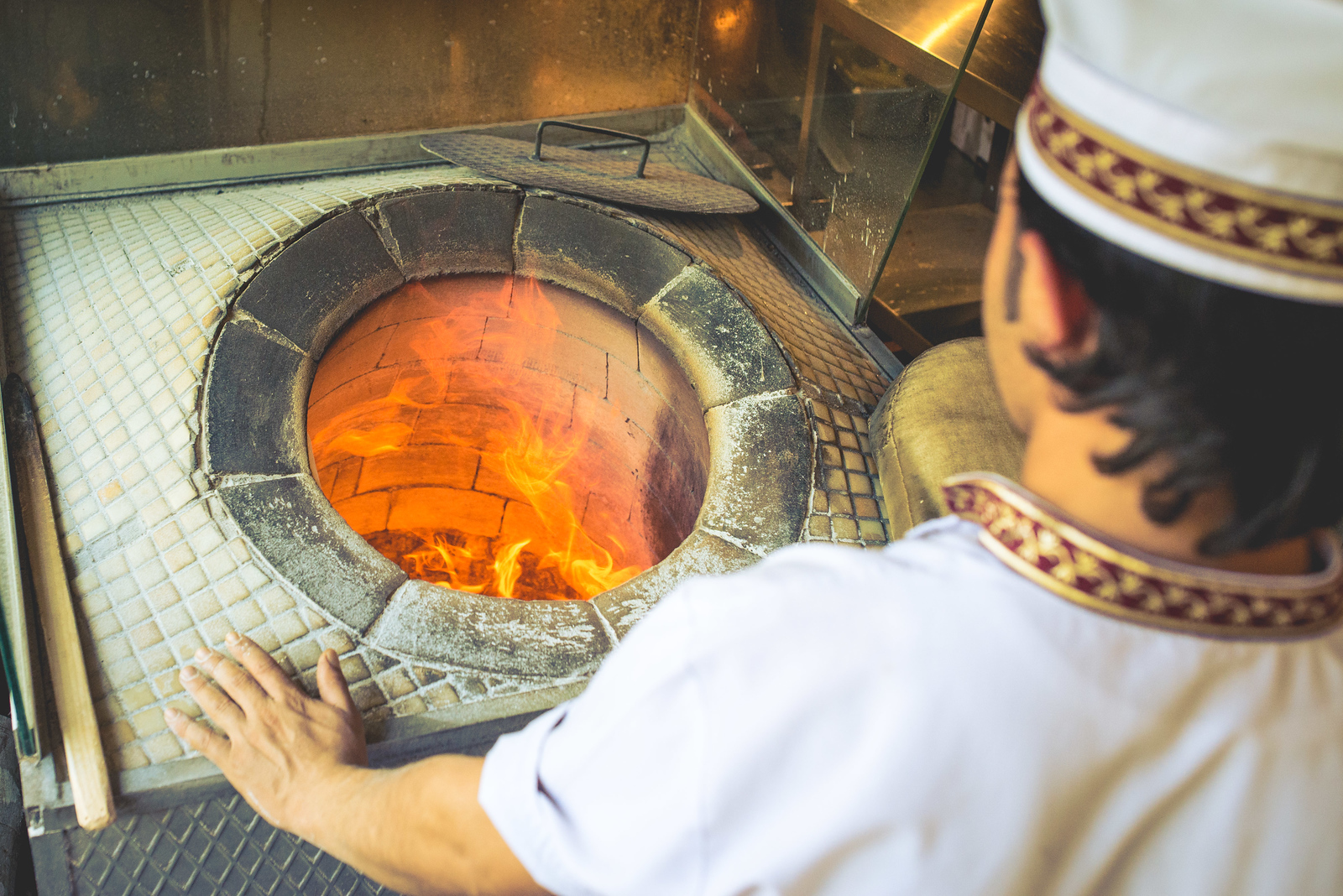 A bread maker peers into the fiery oven before throwing Turkish flat bread on the brick.