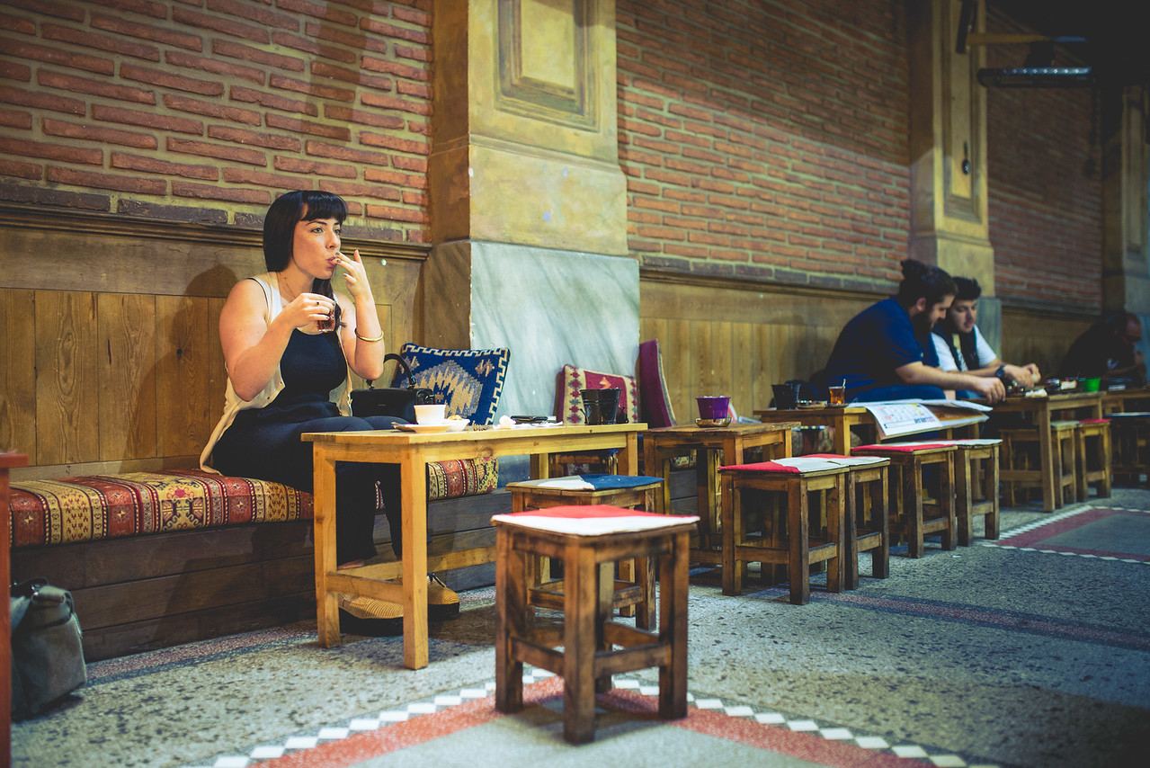 A young lady eats sweets and drinks tea in an charming old passage complete with tiny stools and textured cushions.