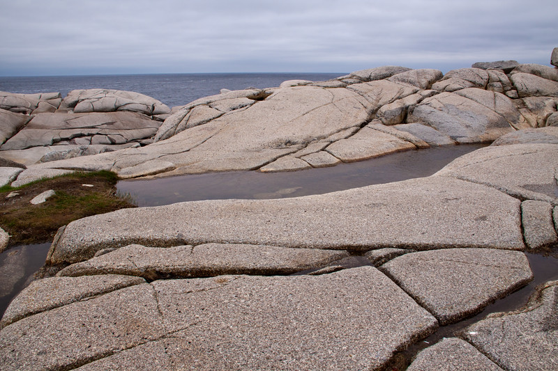 Cold, rainy day and rocky coastline at Peggy's Cove fishing village near Halifax, Nova Scotia, Canada.
