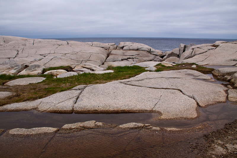 Cold, rainy day and rocky coastline at Peggy's Cove fishing village near Halifax, Nova Scotia, Canada.