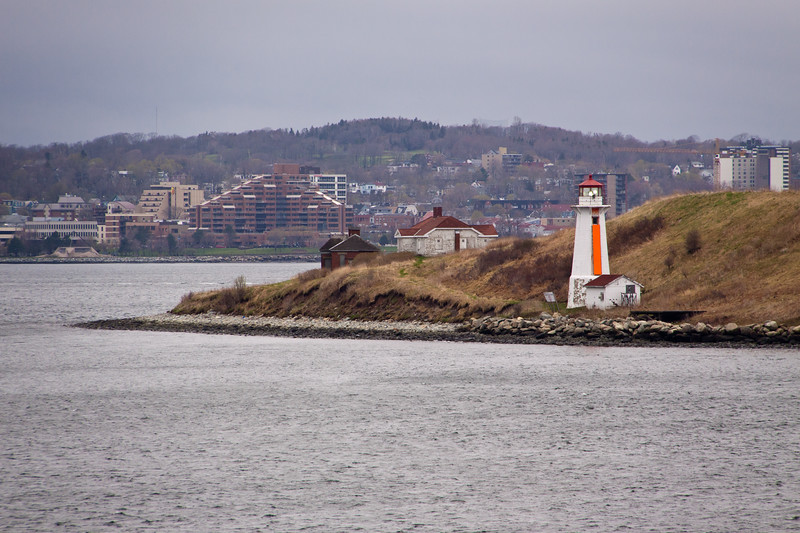 Georges Island Lighthouse, Halifax harbor, Halifax, Nova Scotia, Canada. First lighthouse erected in 1876. The current lighthouse, erected in 1917, is an octagonal concrete structure surmounted by an aluminum lantern. The tower is painted white and the lantern red. There is a fluorescent red vertical stripe as a daymark on the south side which faces the mouth of the harbour.
