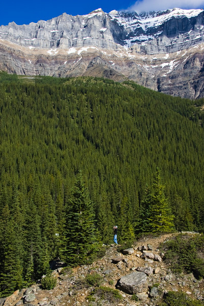 Hiker climbing up to get a better view of Moraine Lake and the Valley of Ten Peaks, in Banff National Park, Alberta, Canada.
