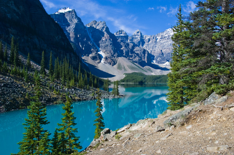 Moraine Lake in Banff National Park, Alberta, Canada. Moraine Lake is a glacially-fed lake in Banff National Park, 14 kilometres (8.7 mi) outside the Village of Lake Louise, Alberta, Canada. It is situated in the Valley of the Ten Peaks, at an elevation of approximately 6,183 feet (1,885 m). The lake has a surface area of .5 square kilometres (0.19 sq mi).<br /> The lake, being glacially fed, does not reach its crest until mid to late June. When it is full, it reflects a distinct shade of blue. The color is due to the refraction of light off the rock flour deposited in the lake on a continual basis.