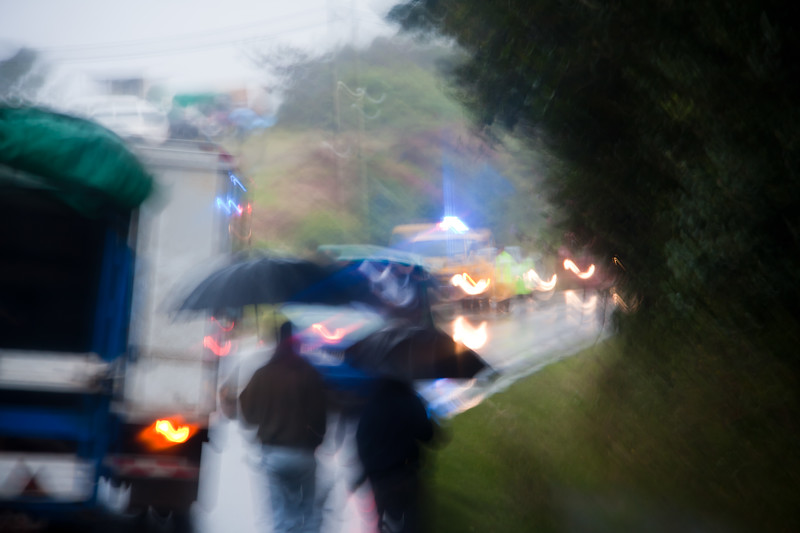 Abstract image of Costa Ricans waliking in the rain for a funeral. This is on the Pan American Highway and all traffic slows to a crawl as the funeral proceeds.