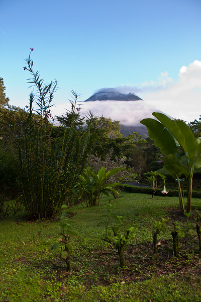 Arenal Observatory Lodge, near Fortuna, Costa Rica, with Arenal Volcano in the distance. Volcano is active, with smoke trails visible.