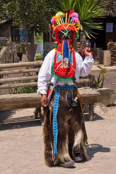 Ecuadorian native in El Diablo costume at equator museum near Quito.