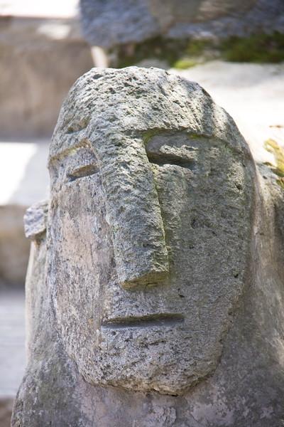 Carved faces in stone in Ecuador museum.