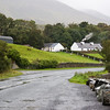 Irish Cottage with Smoke with rock fence and sheep, on road in County Mayo