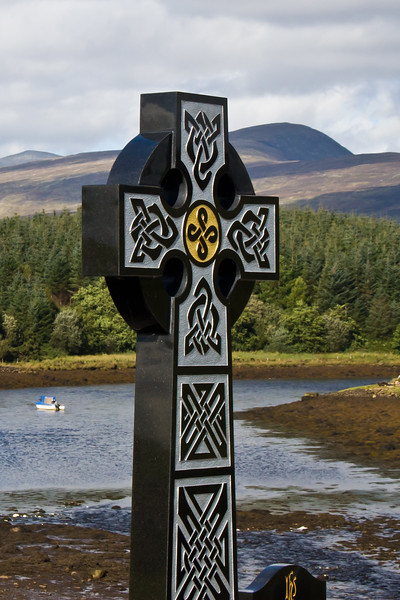 Celtic Cross overlooking lake and mountains at Burrishoole Abbey in County Mayo, Ireland