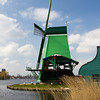 Working windmills at Zaanse Schans park and museum in North Holland, The Netherlands. This park and museum is a national effort to preserve Holland's history and culture. It is a working village where people live in homes that were typical of Holland's past. Exhibitions of old crafts (such as making wooden shoes, or making cheese) are offered daily.