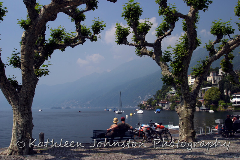 A couple rests at water's edge on Lago Maggiore in Ascona, Switzerland at the border of Italy.