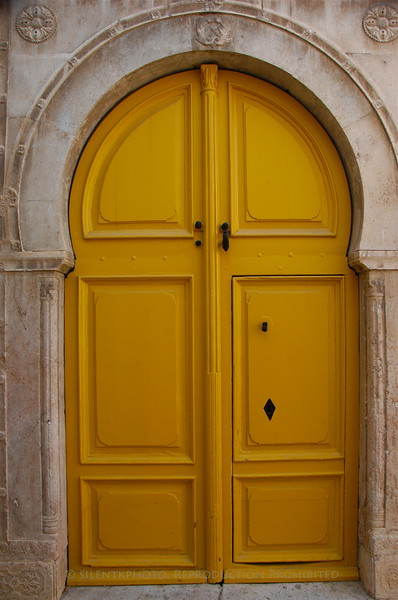 A yellow door opening to a local residence.