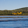 Small airplane on Comal River in Fairbanks, Alaska. As part of tour, pilot is demostrating quickness of takeoff and landing for small airplanes and bush pilots. Seaplanes and airplanes are often the only means of access to remote areas in Alaska. This pilot is taking off and landing on a small sand bar in the river.