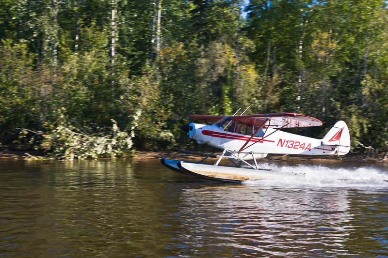 Seaplane on Comal River in Fairbanks, Alaska. As part of tour, pilot is demostrating quickness of takeoff and landing for small seaplanes and bush pilots. Seaplanes and airplanes are often the only means of access to remote areas in Alaska.