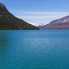 Turquoise waters of Kenai Lake with snow covered Kenai Mountain Range in distance, near Seward, Alaska.